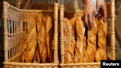 FILE - A French baker places freshly-baked baguettes, the traditional French bread, in wicker baskets in his shop in Strasbourg, eastern France, Aug. 6, 2010.