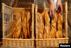 A baker places freshly-baked baguettes, the traditional French bread, in baskets in his shop in Strasbourg, eastern France, Aug. 2010.