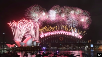 fireworks explode over the opera house and the harbour bridge during new years eve celebrations in