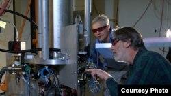 فیزیکدان موسسه ملی استانداردها و تکنولوژی آمريکا، استیون جفرتس (جلو) و تام هونر با NIST-F2 چشمه سزیوم ساعت اتمی، که استانداردی جديدی برای زمان غیر نظامی ایالات متحده خواهد بود.