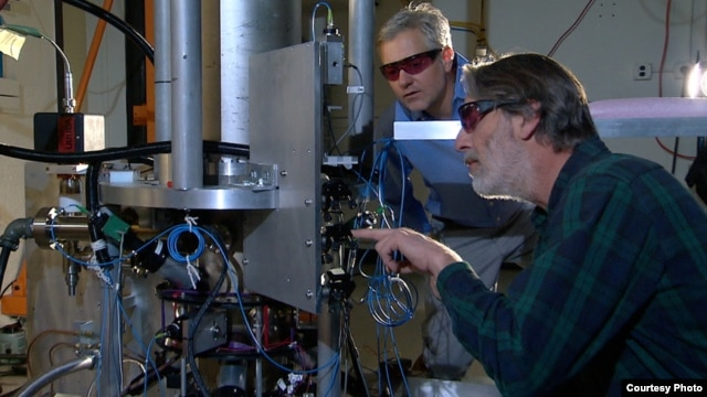 "NIST physicists Steve Jefferts (foreground) and Tom Heavner with the NIST-F2 ""cesium fountain"" atomic clock, a new civilian time standard for the United States."