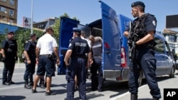 FILE - Kosovo police officers escort a Kosovo Albanian man suspected of fighting alongside Islamic radicals in Iraq and Syria to a local court in Pristina, Tuesday, Aug. 12, 2014. Kosovo police on Monday arrested at least 40 people in a major operation ta
