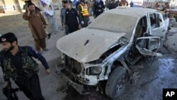 A policeman walks past a vehicle damaged by a suicide bomb attack on the outskirts of Peshawar January 31, 2011.