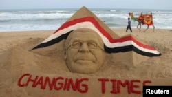 A man with his camel walks near a sand sculpture of Egypt's ousted president Mohamed Morsi created by Indian sand artist Sudarshan Patnaik at the golden sea beach in Puri, about 65 km (40 miles) from the eastern Indian city Bhubaneswar July 5, 2013.