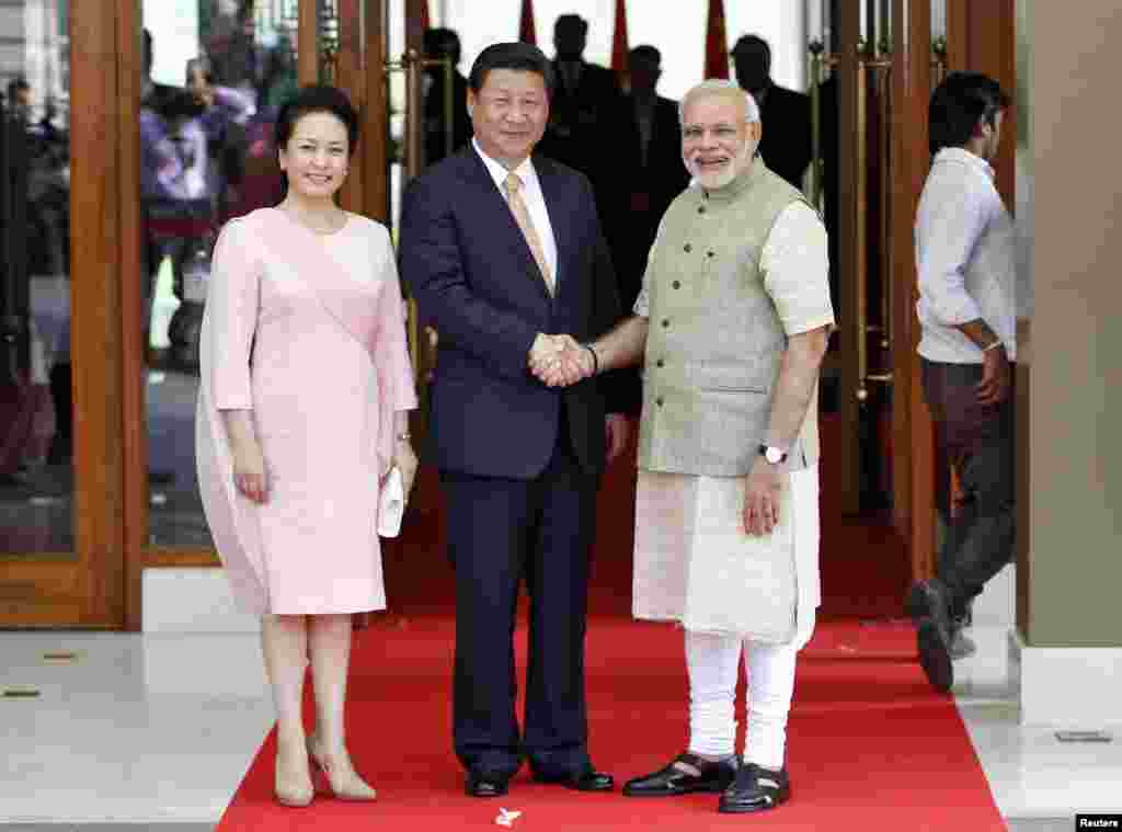 India's Prime Minister Narendra Modi (right) and China's President Xi Jinping shake hands as Xi's wife Peng Liyuan looks on before their meeting in the western Indian city of Ahmedabad, Sept. 17, 2014.