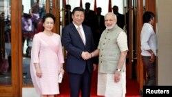 中国国家主席习近平访问印度,和印度总理纳伦德拉•莫迪(右)握手。站在左边的是习近平夫人彭丽媛(2014年9月17日)