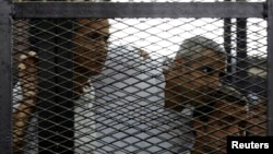 FILE - From left, Peter Greste, Mohamed Fahmy and Baher Mohamed listen to the ruling at a court in Cairo, Egypt.
