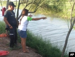 In this Sunday, June 23, 2019 photo, Tania Vanessa Ávalos of El Salvador speaks with Mexican authorities after her husband and nearly two-year-old daughter were swept away by the current in Matamoros, Mexico, while trying to cross the Rio Grande.