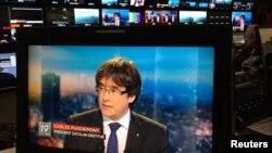 Presiden Catalonia yang digulingkan, Carles Puigdemont tampil pada layar televisi saat wawancara langsung di sebuah bar di Brussels, Belgia, 3 November 2017.
