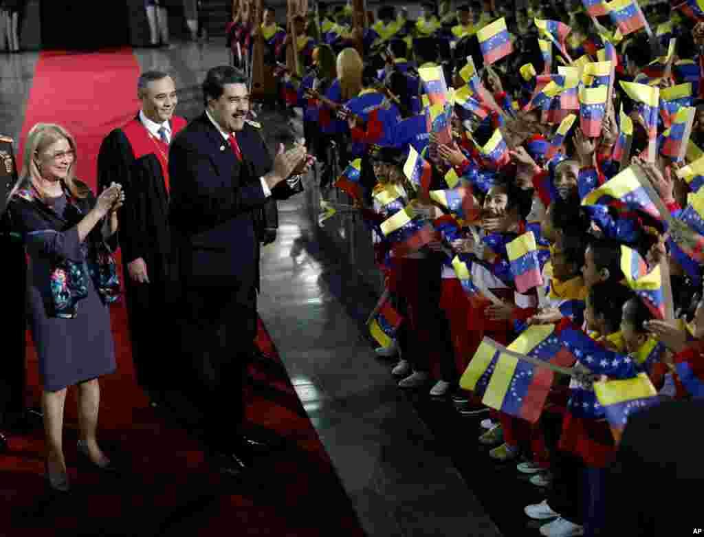 ប្រធានាធិបតីវេណេស៊ុយអេឡា លោកNicolas Maduro និងស្ត្រីទីមួយCilia Flores ឈប់ដើម្បីស្វាគមន៍ដល់ក្រុមក្មេងៗដែលកំពុងគ្រវីទង់ជាតិ នៅពេលលោកមកដល់តុលាការកំពូលដើម្បីចូលរួមពិធីចូលកាន់តំណែងជាប្រធានាធិបតីបន្ត នៅទីក្រុងការ៉ាកាស ប្រទេសវេណាស៊ុយអេឡា។