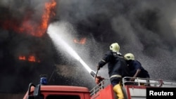 Firemen try to extinguish a fire at Great Nigeria Insurance House in Lagos business district November 4, 2013. There have been no casualties reported, and the cause of the fire is as yet unknown. REUTERS/Akintunde Akinleye (NIGERIA - Tags: DI