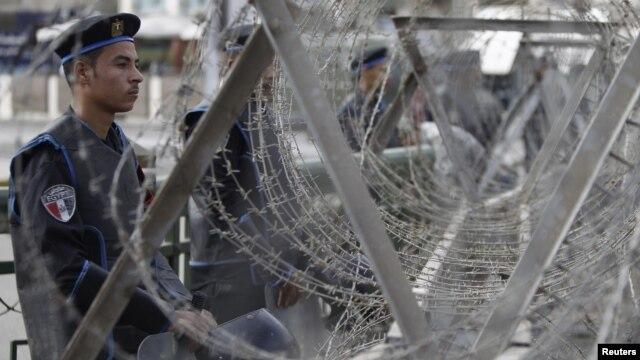 Cảnh sát chống bạo động Ai Cập sau hàng rào dây thép gai trước dinh tổng thống ở Cairo, ngày 4/12/2012.