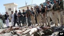 4일 아프가니스탄 탈레반 무장조직의 공격이 있었던 가즈니 주 정부 청사에서 정부군 병사들이 사망한 탈레반 조직원들의 시신 옆에 서 있다.