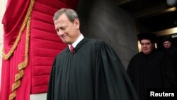 Supreme Court Chief Justice John Roberts is followed by Supreme Court Justice Antonin Scalia as they arrive for the presidential inauguration on the West Front of the U.S. Capitol in Washington January 21, 2013