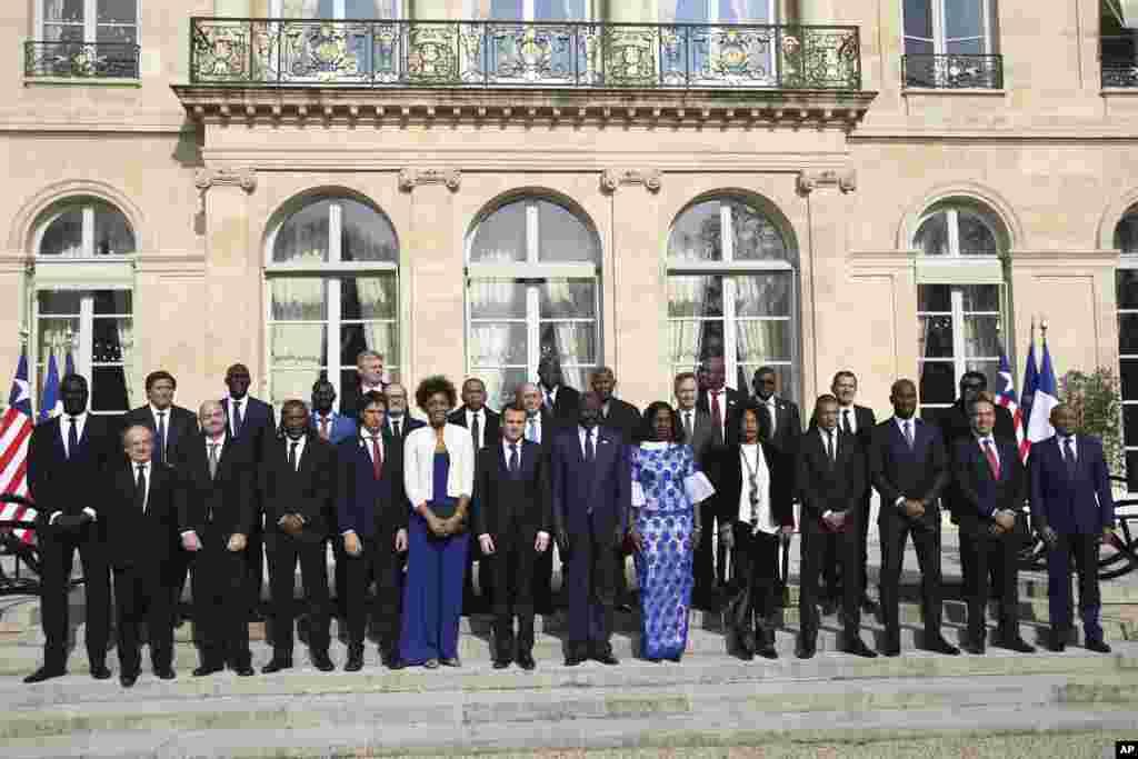 Le président français, Emmanuel Macron, son homologue George Weah et des invités posent pour une photo avant un déjeuner à l'Elysée, à Paris, le 21 février 2018.