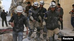 Rescuers walk on the rubble of collapsed buildings after what activists said was an airstrike by forces loyal to Syrian President Bashar al-Assad in Aleppo, Feb. 14, 2014.