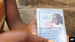 A mother shows the identification of her son who was killed in one of the many recent pro-democracy protests in Guinea.