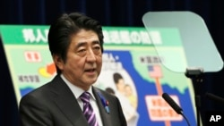Japanese Prime Minister Shinzo Abe speaks to reporters July 1, 2014 about possible changes to the country's constitution..