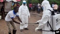 Des agents de santé venant de prendre un échantillon de sang d'un enfant à tester pour le virus Ebola dans une zone où un garçon de 17 ans est mort du virus en périphérie de Monrovia, au Libéria, 30 juin 2015. (AP Photo/ Abbas Dulleh,File)