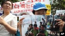 一名北韓變節者在韓國抗議老撾遣返朝鮮青少年的活動中,手持其中一個朝鮮青少年的照片