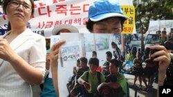 An unidentified North Korean defector holds a picture of nine apparent North Korean defectors who were flown home as she cries during a rally protesting against Laos' repatriation of them, in Seoul, South Korea, June 5, 2013.