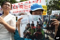 FILE - An unidentified North Korean defector holds a picture of nine North Korean defectors who were flown home as she cries during a rally protesting Laos' repatriation of them, in Seoul, South Korea, June 5, 2013.