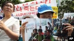 Người biểu tình cầm hình ảnh 9 thanh niên Bắc Triều Tiên đào thoát bị trả về nước.
