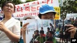 Para pembelot tak dikenal Korea Utara memegang gambar sembilan pembelot Korea Utara yang diterbangkan pulang ke negaranya dari Laos sambil menangis dalam aksi protes di Seoul, Korea Selatan (5/6). Korea Selatan menolak tuduhan Korea Utara yang menyebutkan keterlibatan pemerintah Korea Selatan dalam penculikan tersebut.