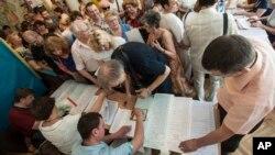 Electores se aglomeran en un colegio electoral en Kiev para recibir sus boletas de votación.
