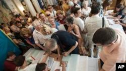 Warga Ukraina memberikan suara dalam pemilihan Presiden di Kyiv, hari Minggu (25/5).