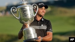 Jason Day, of Australia, holds up the Wanamaker Trophy after winning the PGA Championship golf tournament Sunday, Aug. 16, 2015, at Whistling Straits in Haven, Wis.