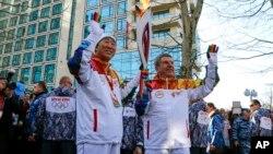 Chủ tịch Ủy ban Olympic Quốc tế Thomas Bach (phải) chuyền ngọn đuốc cho Tổng thư ký LHQ Ban Ki-moon bên dòng sông Sochi, 6/2/14