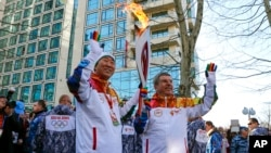 IOC President Thomas Bach, right, hands over the Olympic torch to United Nations Secretary-General Ban Ki-moon as the torch relay arrives in Sochi, ahead of the 2014 Winter Olympics, Feb. 6, 2014, in Russia.