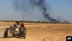 Asap membubung dari pertempuran antara pasukan keamanan Irak dan ISIS, sementara warga mengungsi di Hit, Irak, April 2016. (AP/Khalid Mohammed)