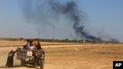 In this April 4, 2016 file photo, smoke rises as people flee their homes during clashes between Iraqi security forces and members of the Islamic State group in Hit, Iraq.