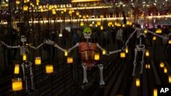 En México, esqueletos de papier-mache representan a rescatistas y voluntarios que trabajaron luego del terremoto del pasado septiembre, se muestran en un altar en honor de las víctimas del sismo durante las festividades en el Zócalo, la plaza principal de la capital mexicana. Oct. 30, 2017.