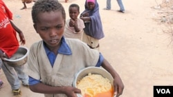 Boy with pot of gruel camp at Badbaado IDP camp in Mogadishu, Somalia. (VOA - P. Heinlein)