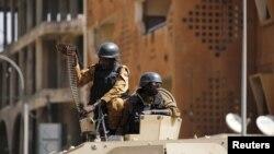Des militaires burkinabè préparent une mitraillette posée un char déployé à l'extérieur de l'hôtel Splendid après l'attentat qui a fait 30 morts à Ougadougou, Burkina Faso, 18 janvier 2016.