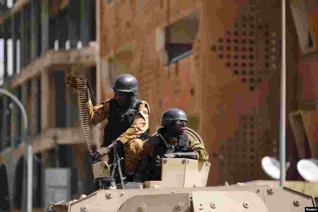 Soldiers stand guard in an armored vehicle outside the Splendid Hotel after al-Qaida militants killed at least 28 people in an attack on the hotel and a restaurant in Ouagadougou, Burkina Faso.