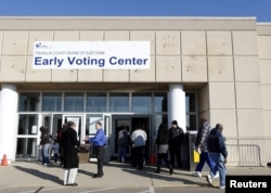 FILE - Voters walk into the Franklin County in-person absentee voting location to cast ballots in Columbus, Ohio, Nov. 5, 2012.