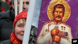 A woman holds a portrait of Soviet dictator Josef Stalin during a communist rally marking Defenders of the Fatherland Day, Moscow, Feb. 23, 2013.