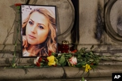 FILE - A portrait of slain television reporter Viktoria Marinova is placed on the Liberty Monument next to flowers and candles during a vigil in Ruse, Bulgaria, Oct. 9, 2018.
