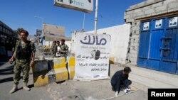 Dân quân Houthi canh gác trong khi 1 chuyên gia kiểm tra hiện trường vụ nổ gần dinh Cộng hòa ở Sana'a, 7/2/2015.