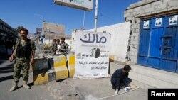 Cumhurbaşkanlığı sarayı yakınında patlayan bombayı inceleyen uzmanın başında bekleyen bir Husi milisi