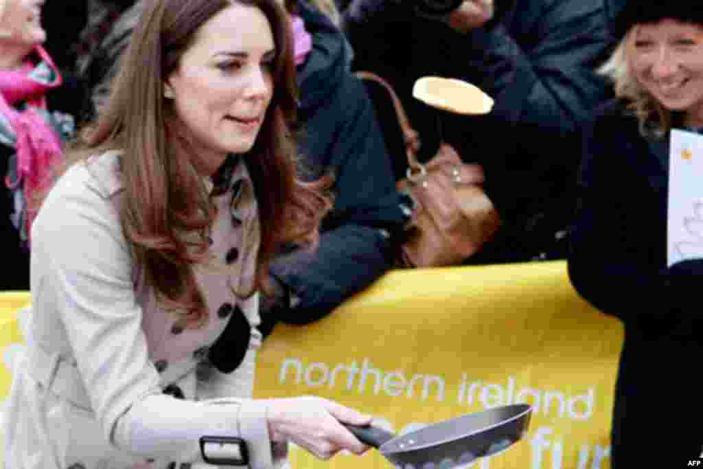Kate Middleton flips a pancake at a display by the charity Northern Ireland Cancer Fund for Children, outside the City Hall in Belfast, Northern Ireland, Tuesday March 8, 2011.