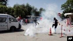 Pendukung tokoh oposisi Tunisia Mohammed Brahmi berupaya melarikan diri dari gas air mata yang ditembakkan polisi, saat berlangsungnya bentrokan pasca pemakaman tokoh oposisi tersebut di Tunis (27/7).