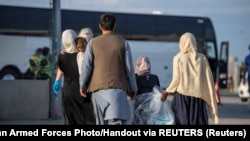 Afghan refugees who supported Canada's mission in Afghanistan prepare to board buses after arriving in Canada, at Toronto Pearson International Airport August 24, 2021.