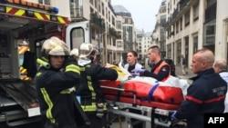消防人员用担架把伤员抬走。背后是发生枪击的法国讽刺漫画周刊《查理周刊》所在的大楼,2015年1月7日