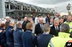 Thủ tướng Bỉ Charles Michel (giữa) bắt tay các sĩ quan cảnh sát và những người phản ứng đầu tiên ở phía trước sân bay Zaventem bị hư hại tại Brussels ngày 23 tháng 3 năm 2016.