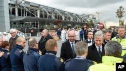 Le Premier ministre belge Charles Michel, au centre, serre la main des policiers et des premiers secours en face du terminal de l'aéroport endommagé Zaventem à Bruxelles le 23 Mars 2016. (AP Photo/Frederic Sierakowski)